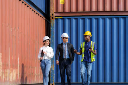 African american foreman is explaining the various sections of the container depot terminal to a caucasian man manager, with a female secretary next to him.