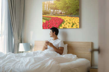 An Asian man sits in bed with a white blanket and checking his email on his cell phone in the morning at home before taking a shower. Banco de Imagens
