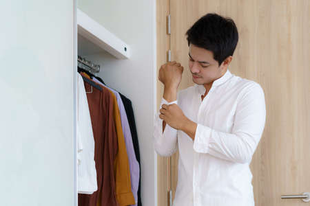 Asian man are buttoned up their shirts to get dressed, getting ready to go to work in the morning in the dressing room at home.