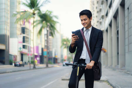 Asian businessman is riding an electric scooter and using his mobile phone to open a map in application to check the city road routes to work in the morning. Banco de Imagens