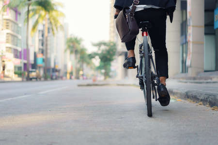 Close up of foot businessman is riding a bicycle on the city streets for his morning commute to work. Eco Transportation Concept.