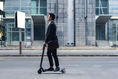 Asian businessman riding an electric scooter on the city streets to go to work in the morning. Daily commute that best reflect the working world of today. Banco de Imagens