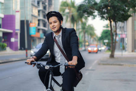 Asian businessman in a suit is riding a bicycle on the city streets for his morning commute to work. Eco Transportation Concept.