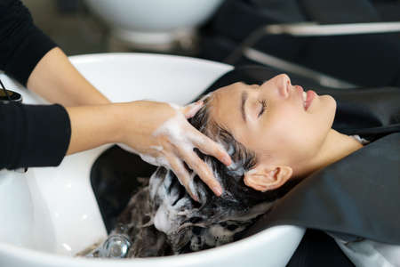 hairdresser is applying shampoo and massaging hair of a customer. Woman having her hair washed in a hairdressing salon. Banco de Imagens