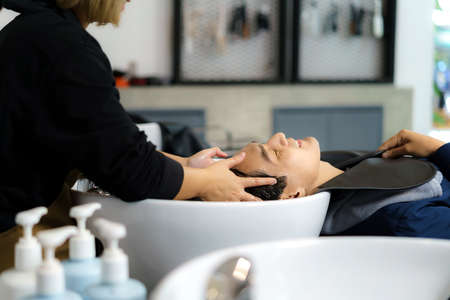 Hairdresser is applying shampoo and massaging hair of a customer. man having her hair washed in a hairdressing salon.
