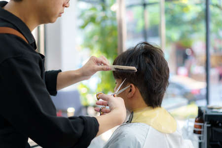 Barber trims the hair of a young man with scissors in his barbershop