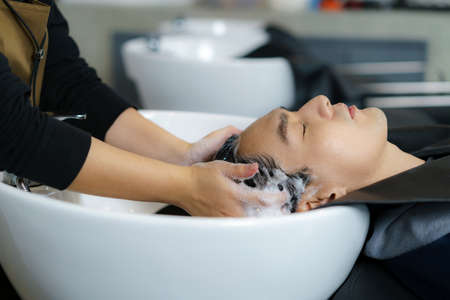 Hairdresser is applying shampoo and massaging hair of a customer. man having his hair washed in a hairdressing salon.