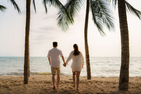 Asian couple is running and holding hands on a beachfront beach sea with coconut trees while on vacation in the summer in Thailand.