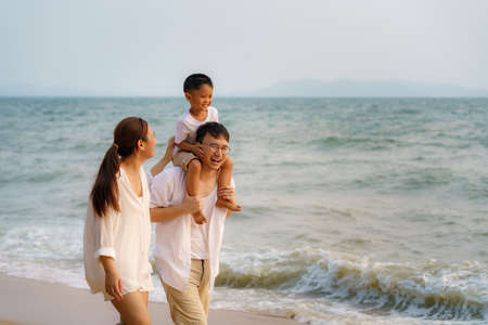 Asian family with fathers carrying his son on back and mother walking togerther along a beachfront beach while on vacation in the summer in Thailand.
