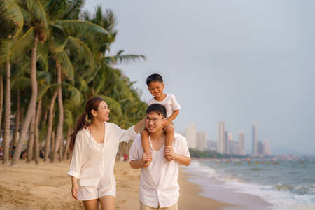Asian family with fathers carrying his son on back and mother walking togerther along a beachfront beach with coconut trees while on vacation in the summer in Thailand.