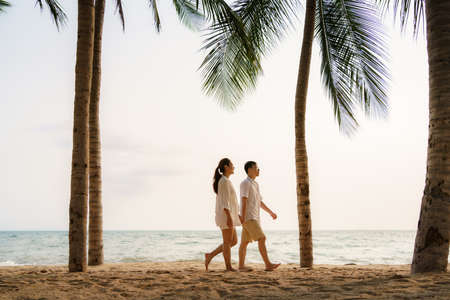 Asian couple is walking and holding hands on a beachfront beach sea with coconut trees while on vacation in the summer in Thailand.