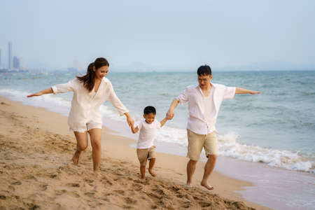 Asian family with fathers, mother and son are running along a beachfront beach while on vacation in the summer in Thailand. Banco de Imagens