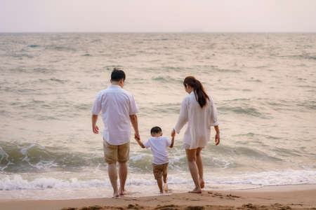 Asian family with fathers, mother and son are playing water sea along a beachfront beach with coconut trees while on vacation in the summer in Thailand. Banco de Imagens