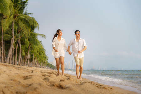 Asian couple is running and holding hand on a beachfront beach sea with coconut trees while on vacation in the summer in Thailand.