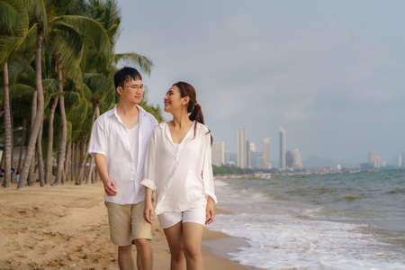 Asian couple is walking and hugging on a beachfront beach sea with coconut trees while on vacation in the summer in Thailand.