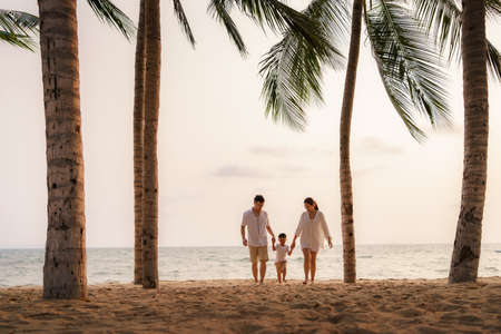 Asian family with fathers, mother and son are walking along a beachfront beach with coconut trees while on vacation in the summer in Thailand.