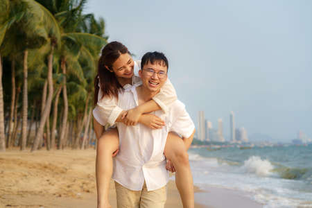 Asian man carry her girlfriend on his back and have fun on a beach with coconut palms while relaxing on a summer vacation. Banco de Imagens
