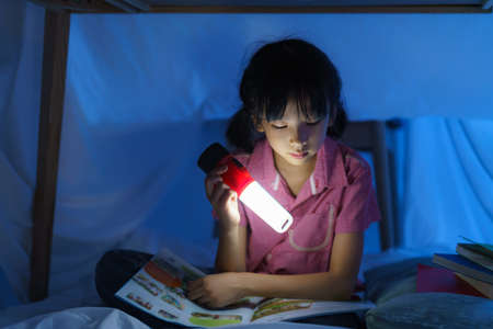 Asian girl child to make a camp to play imaginatively and reading book by flashlight  in living room at home.