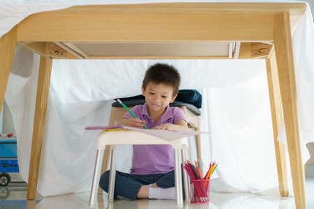 Asian preschool boy drawing in paper while lying in a blanket fort in living room at home for perfect hideout away from their other family members and for them to play imaginatively.