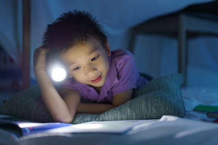 Asian preschool boy child to make a camp to play imaginatively and reading book by flashlight  in living room at home.