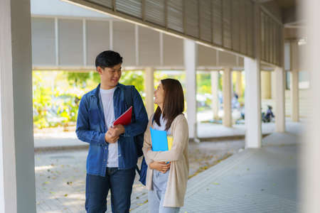 Two Asian couple university students walking and talking to class in walkway on a beautiful sunny day in campus. Banco de Imagens