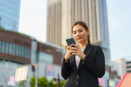 Asian executive working woman using a mobile phone in the street with office buildings in the background in Bangkok, Thailand. Banco de Imagens