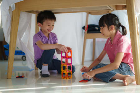Asian sibling playing building block while sitting in a blanket fort in living room at home for perfect hideout away from their other family members and for them to play imaginatively. Banco de Imagens