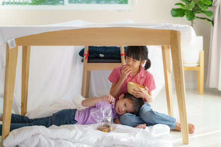Asian cute little boy feeding snack to his sister sibling while sitting in a blanket fort in living room at home for perfect hideout away from their other family members and for them to play imaginatively.
