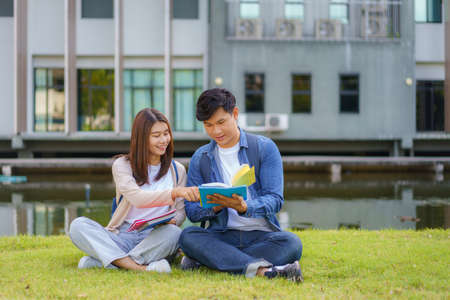 Portrait of Asian man and woman university student aitting on grass in campus looking at camera and smile and reading a book togerter in park.