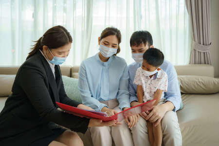 Asian woman's insurance broker is offering details of health insurance coverage for  to Asian family with father, mother and son in their living rooms at home.
