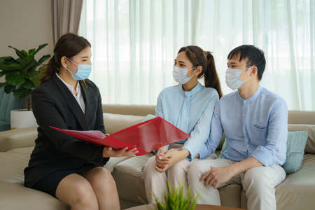 Asian woman's insurance broker is offering details of health insurance coverage for   to Asian couple in their living rooms at home.
