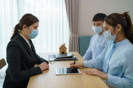 Asian woman's real estate agents are having clients sign contracts to sell their homes in digital tablet while wearing marks to prevent the spread