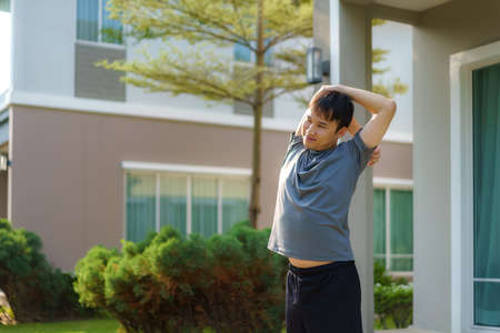 Asian man stretching to warm up or cool down, before or after exercise, near the front door in the neighborhood for daily health and well being, both physical and mental.