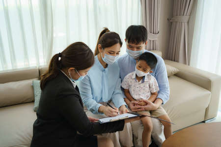 Asian woman's insurance broker is offering details of health insurance coverage for    Asian family with father, mother and son in their living rooms at home. Banco de Imagens