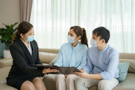 Asian woman's insurance broker is offering details of health insurance coverage for   Asian couple in their living rooms at home. Banco de Imagens