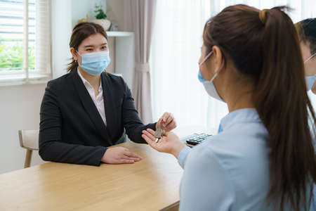 Asian Real estate agent woman give keys to customer after signing contract to buy house, insurance or loan real estate while wearing masks to prevent the spread