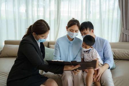 Asian woman's insurance broker is offering details of health insurance coverage for Asian family with father, mother and son in their living rooms at home.