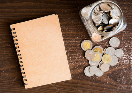 argent: financial and investment concept,saving coin on jar with wooden background Stock Photo