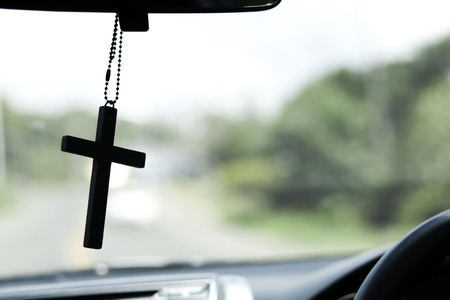 Crucifix in front of on the car and road trips