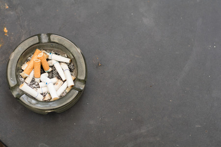 Carcinogens in the ashtray placed on a steel table background. Banque d'images