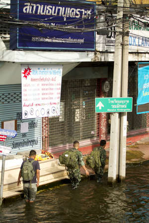 wade: BANGKOK, THAILAND - NOV 12: Soldier patrol wade in flood water after the city was flooded on November 12, 2011 in Bangkok, Thailand.