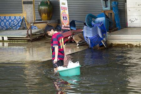 BANGKOK, THAILAND - NOV 12: A man using green basin load stuff after the city was flooded on November 12, 2011 in Bangkok, Thailand.