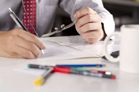 working hard, a businessman hold his glasses and write down his job.