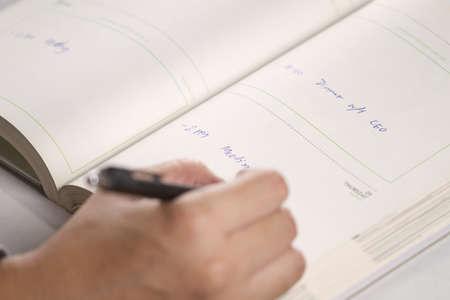 メモ、スケジュール メモ整理帳に書いて男性手。