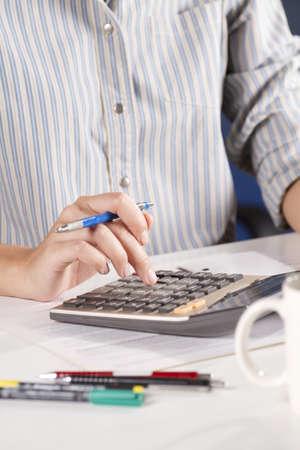 calculate, female model holding pencil using calculator. photo