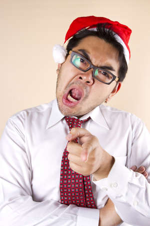 angry Santa, Businessman wear Santa hat pointing look frown and angry. photo