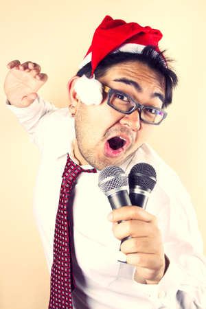 Singing Santa, businessman wear Santa hat singing with two microphone. Stock Photo