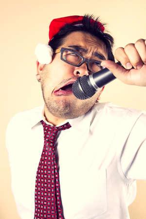 winter party: Karaoke Babbo Natale, uomo d'affari che indossa cappello santa cantando con microfono.