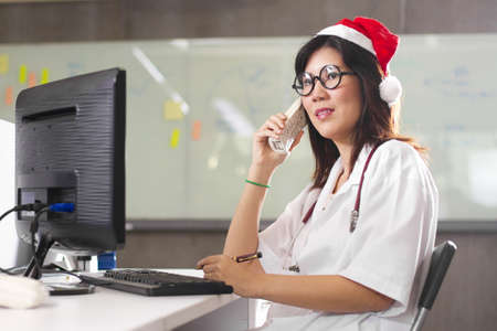 Doctor Santa phone, Female Santa wearing doctor costume with Santa red hat on the phone. photo