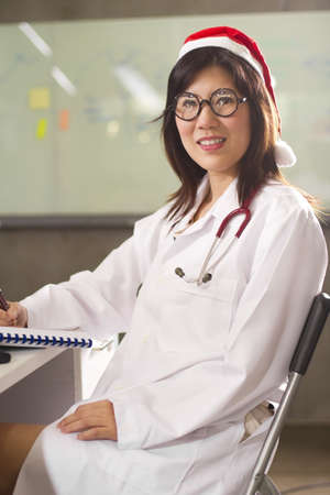 Santa doctor, Female Santa wearing white gown , stethoscope and Santa hat. photo
